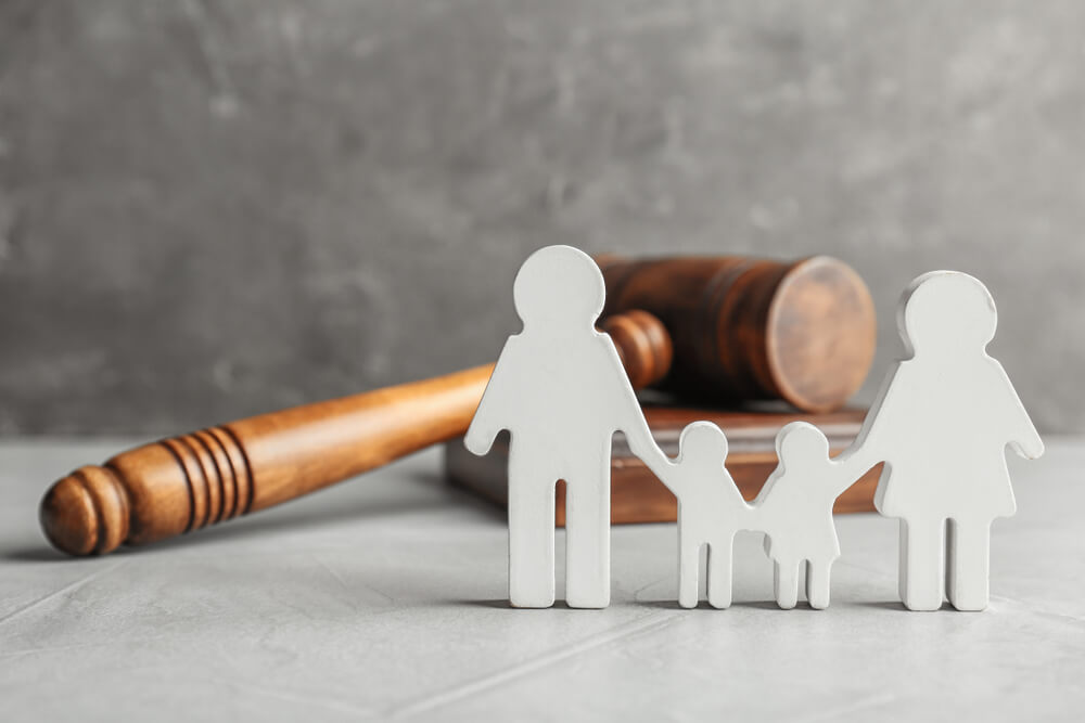 A white block cutout of a family stands in front of a gavel, symbolizing child support.